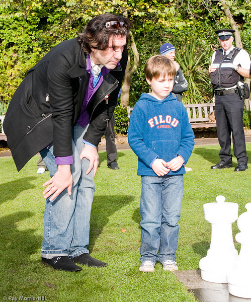 Jason Kouchak gives advice while the chess police look on