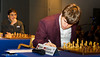 Round 3: Magnus Carlsen with Viswanathan Anand in the background