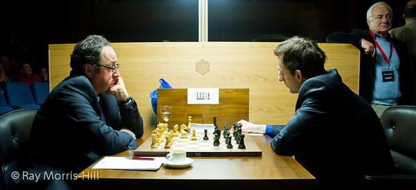 Round 14: Boris Gelfand vs Alexander Grischuk.  Genna Sosonko looks on.