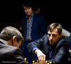 Alexnader Grischuk makes his move against Peter Svidler in Round 2.   Teimour Radjabov watches.