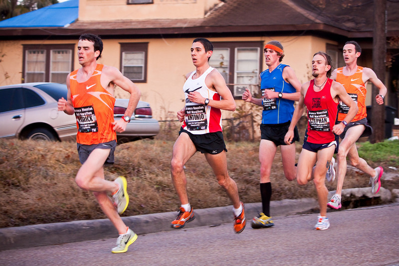 Pictured at MIle 6 (Studemont & White Oak) is the Half Marathon winner  Antonio Vega (white jersey) who completed the 13.1 mile race in 1:01:54.  Also shown is Patrick Smyth (fron orange jersey), 2nd place, and Brent Vaughn (back orange jersey)