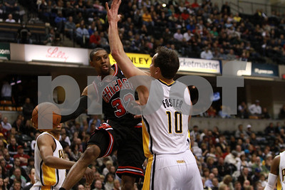 1/14/11- Chicago Bulls guard C.J. Watson (#32)  passes the ball around Indiana Pacers Jeff Foster (#10), as the Chicago Bulls prevailed 99-86. Photo/Ron Foster Sharif
