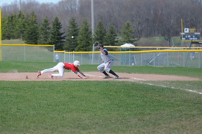 Austin Issette dives back to first base in the first game of a doubleheader with Big Rapids Tuesday, May 6, 2014.  Joe Buczek - The Morning Sun