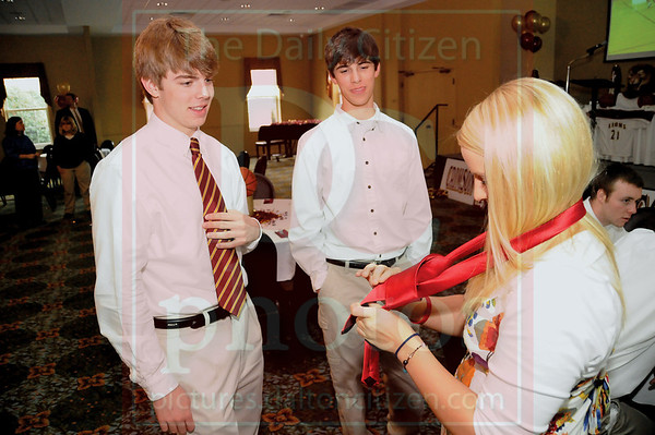 Matt Hamilton/The Daily Citizen<br /> Ivy Acres, left, and Rollins Jolly look on as cheerleader Megan Jennings attempts to tie a neck tie for Jolly before the Christian Heritage basketball banquet Thursday at 1st Baptist Church.