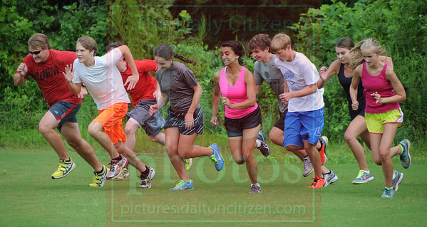 Matt Hamilton/The Daily Citizen<br /> CHS xc coach, far left, runs with his team during practice Tuesday.
