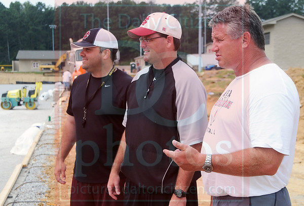 Matt Hamilton/The Daily Citizen<br /> From left, Heath Patterson, Preston Poag and Bill Mitchell look in on the progress at new Christian Heritage football field Saturday.