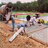 Matt Hamilton/The Daily Citizen<br /> Workers lay concrete at the new Christian Heritage football field Saturday.