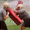 Matt Hamilton/The Daily Citizen<br /> Mac Raughton holds a bag as Noah Holsomback drives him back during practice Friday.