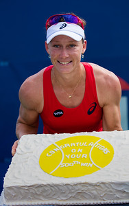 Samantha Stosur, of Australia, poses with celebratory cake after clinching her 500th career win against Kristina Mladenovic, of France, in the women's singles first round.