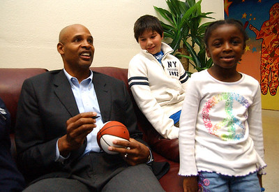 Clark Kellogg, left, former NBA and Ohio State player, signs a ball for Wes Gerhardt, 12, of Lakewood, and McKenzie Wright, 6, of Lorain, at the Boys and GIrls Club in Elyria Oct. 15.   Steve Manheim/CT