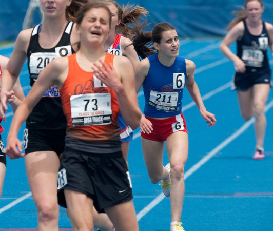 Byron senior Kelsey Hildreth (73, foreground) reacts while crossing the finish line in first place, ahead of St. Anthony freshman Anna Sophia Keller (211, background) during the Class 1A 3200-meter final at Eastern Illinois University. Keller was in first place before falling near the finish line.