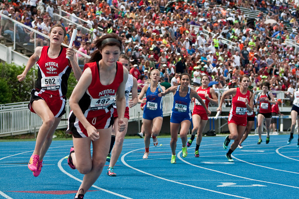 Neoga's Jaycie Roy prepares to hand the baton to Mallori Harshman (left) while Newton's Taylor Johnson hands it to Madison Tinder (center) during the Class 1A 4x200 relay final at Eastern Illinois University.
