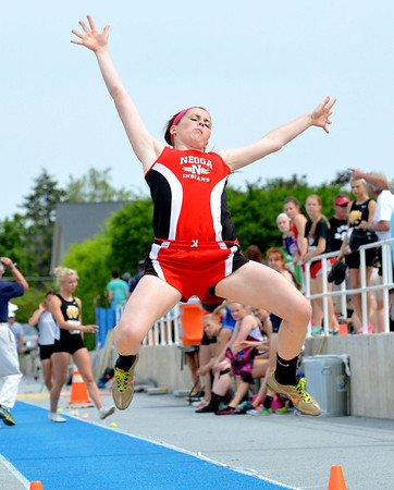 Neoga's Olivia Ott extends her arms and legs outward during her final long jump of the day, which would help her clinch a spot in the finals.