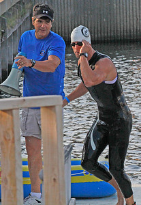 Cleveland Triathlon Swimming section in Cleveland Harbour. adam Kuncel emarges from the swimming section and an official points the way towards the bikes. Photo by Tom Mahl