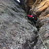 The last pitch - very wet, mossy and chossy chimney action.