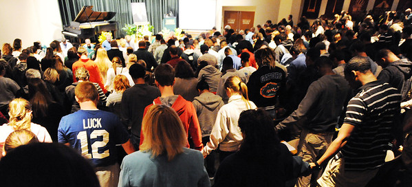 Students, faculty, staff and friends hold hands as they pray during a memorial service in remembrance of Missouri Southern State University assistant football coach Derek Moore Monday evening, Nov. 4, 2013, at MSSU's Corley Auditorium in Webster Hall. The auditorium was filled with standing room only.<br /> Globe | T. Rob Brown