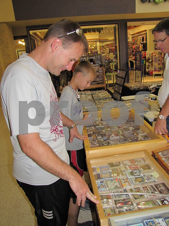 Travis Wirtz and his son Devon look over the vast collection of sports cards at the Crossroads Mall in Fort Dodge.