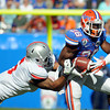 Jan 2, 2012; Tallahassee, FL, USA; Florida Gators running back Jeff Demps (28) runs the ball past Ohio State Buckeyes linebacker Etienne Sabino (6) during the first quarter of the 2012 Gator Bowl at EverBank Field.  Mandatory Credit: Melina Vastola-US PRESSWIRE