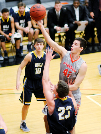 Don Knight | The Herald Bulletin<br /> Anderson University's Nathaniel Acree rolls the ball off his fingertips for a layup against the defense of Mount St. Joseph's Jake Cropper on Wednesday.