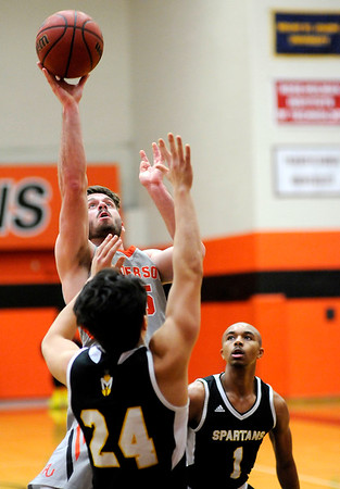 Don Knight | The Herald Bulletin<br /> Anderson University's Mike Peters shoots over Manchester's Keiton Hall on Wednesday.