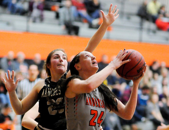 Don Knight | The Herald Bulletin<br /> Anderson University's Payton Moore drives the baseline for a reverse layup as she is guarded by Manchester's Beth Schaefer on Wednesday.