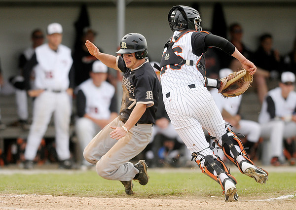 Manchester's Austin Rieke slides into home as he beats the throw to Anderson University catcher Cole Heberling as the Ravens hosted the Spartans on Tuesday.