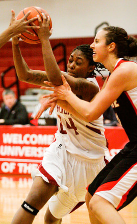 Indiana University Southeast guard Ashmere Woods attempts to drive the ball past Grace College forward Allison Kaufman during their game at IUS on Wednesday. IUS won the game, 68-67. Staff photo by Christopher Fryer