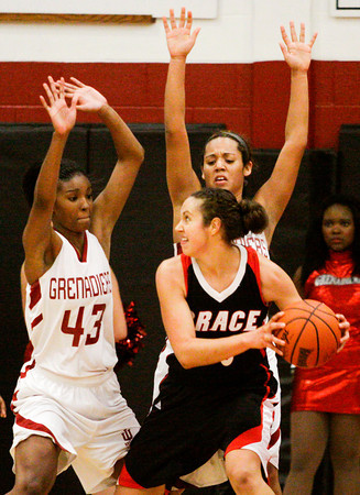 Indiana University Southeast center Kortney Woods, left, and forward Briana Palmer guard Grace College forward Allison Kaufman during their game at IUS on Wednesday. IUS won the game, 68-67. Staff photo by Christopher Fryer