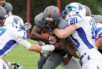 ANNA NORRIS/CHRONICLE Oberlin College running back Moses Richardson pushes the ball through the Case Western Reserve defense on the carry in the second half of the season home opener yesterday at Savage Stadium in Oberlin.