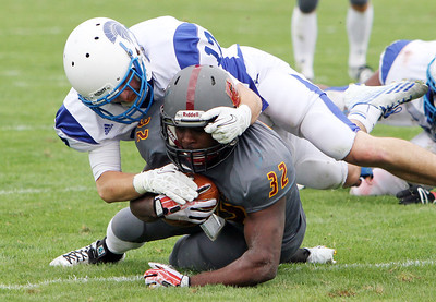 ANNA NORRIS/CHRONICLE Oberlin College running back Moses Richardsons gains yards on the carry as Case Western Reserve's Mike O'Donnell makes the tackle in the second half of the season home opener yesterday at Savage Stadium in Oberlin.