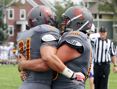 ANNA NORRIS/CHRONICLE Oberlin College's Nick Blaszak (76) hugs running back Blake Buckhannon (21) after Buckhannon scored a touchdown against Case Western Reserve in the fourth quarter of the season home opener yesterday at Savage Stadium in Oberlin.