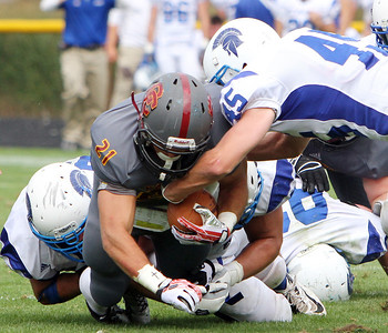 ANNA NORRIS/CHRONICLE Oberlin College running back Blake Buckhannon carries the ball up the middle for a gain of yards as he is tackled by a trio of Case Western Reserve defenders in the second half of the season home opener yesterday at Savage Stadium in Oberlin.