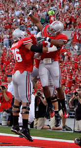 Ohio State's Brandon Saine, right, celebrates his touchdown against Marshall with teammates J. B. Shugarts, left, and Mike Brewster during the first quarter of an NCAA college football game, Thursday, Sept. 2, 2010, in Columbus, Ohio. (AP Photo/Jay LaPrete)
