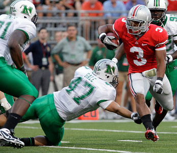 Ohio State's Brandon Saine, right, runs the ball against Marshall's Tyson Gale, center, and Johnny Jones during the first quarter of an NCAA college football game, Thursday, Sept. 2, 2010, in Columbus, Ohio. (AP Photo/Jay LaPrete)