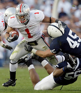 Ohio State running back Dan Herron (1) rushes against Penn State's Eric Latimore (56) and Sean Lee (45) during the first half of an NCAA college football game in State College, Pa., Saturday, Nov. 7, 2009. Ohio State won 24-7.(AP Photo/Carolyn Kaster)