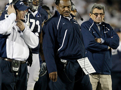Penn State head coach Joe Paterno, right, frowns as he looks at assistant coaches Larry Johnson, center, and Tom Bradley, left, during the second half of an NCAA college football game against Ohio State in State College, Pa., Saturday, Nov. 7, 2009. Ohio State won 24-7(AP Photo/Carolyn Kaster)