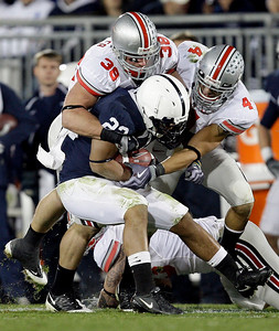 Ohio State's Austin Spitler (38) and Kurt Coleman (4) tie up Penn State running back Evan Royster (22) during the second half of an NCAA college football game in State College, Pa., Saturday, Nov. 7, 2009. Ohio State won 24-7.(AP Photo/Carolyn Kaster)