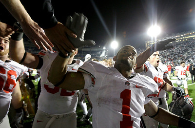 Ohio State's Daniel Herron (1) and members of the Ohio State team celebrate a 24-7 win over Penn State with their student section after an NCAA college football game in State College, Pa., Saturday, Nov. 7, 2009.  (AP Photo/Carolyn Kaster)
