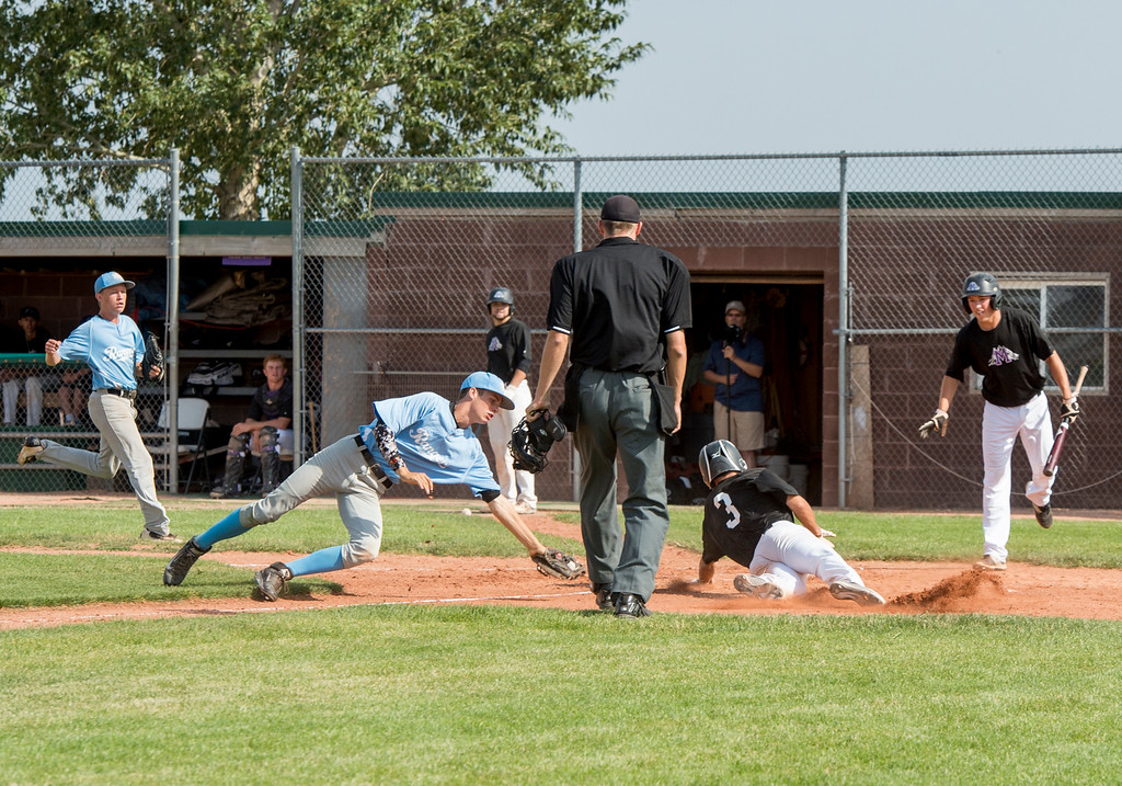 . After nearly getting caught in a run down Mountain View center fielder TJ Felton (3) gets past the tag of Mountain Range short stop Zach Munson (3) Friday afternoon July 15, 2016 to score the first run of the game during the Colorado Baseball League State Tournament at Brock Field in Loveland. (Photo by Michael Brian/Loveland Reporter-Herald)