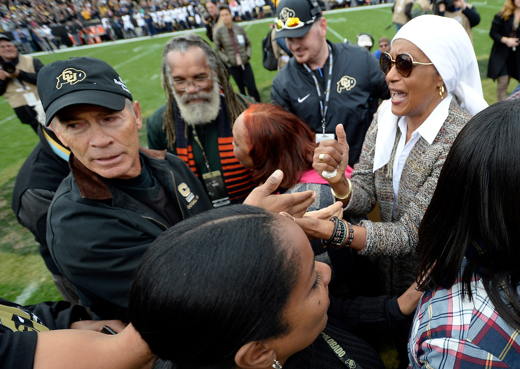 . Bobby Anderson, left, greets Rashaan Salaam\'s mother, Khalada Salaam-Alaji, during a ceremony to retire Salaam\'s number 19, during the CU Cal Homecoming game on Saturday.  Cliff Grassmick / Staff Photographer/ October 28, 2017