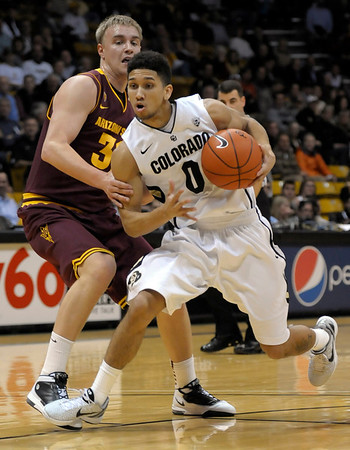 Colorado's Askia Booker (right) runs past Arizona State's Jonathan Gilling (left) during their basketball game at the University of Colorado in Boulder, Colorado January 19, 2012. CAMERA/MARK LEFFINGWELL