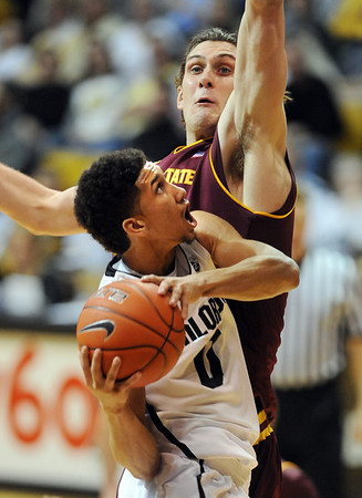 "Askia Booker of CU goes to the basket on Jordan Bachynski of ASU.<br /> For more photos of the game, go to  <a href=""http://www.dailycamera.com"">http://www.dailycamera.com</a>.<br /> January 19, 2012 / Cliff Grassmick"