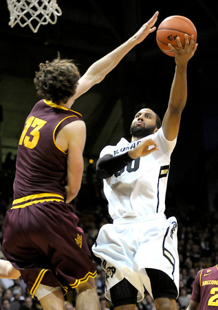 Colorado's Carlon Brown (right) slips a shot by Arizona State's Jordan Bachynski (left) during their basketball game at the University of Colorado in Boulder, Colorado January 19, 2012. CAMERA/MARK LEFFINGWELL