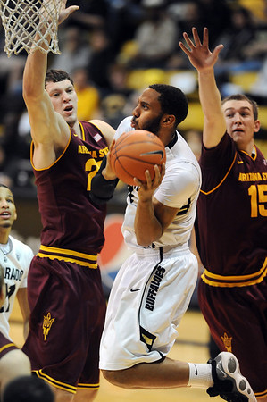 """Carlon Brown of CU drives to the basket between Ruslan Pateev, left, and Chanse Creekmur, both of ASU.<br /> For more photos of the game, go to  <a href=""""http://www.dailycamera.com"""">http://www.dailycamera.com</a>.<br /> January 19, 2012 / Cliff Grassmick"""
