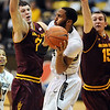 "Carlon Brown of CU drives to the basket between Ruslan Pateev, left, and Chanse Creekmur, both of ASU.<br /> For more photos of the game, go to  <a href=""http://www.dailycamera.com"">http://www.dailycamera.com</a>.<br /> January 19, 2012 / Cliff Grassmick"