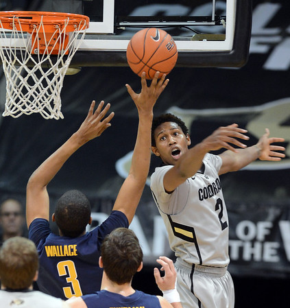 Xavier Johnson of CU tries to block the shot of Tyrone Wallace of Cal during the first half of the January 27th, 2013 game in Boulder.<br /> Cliff Grassmick / January 27, 2013
