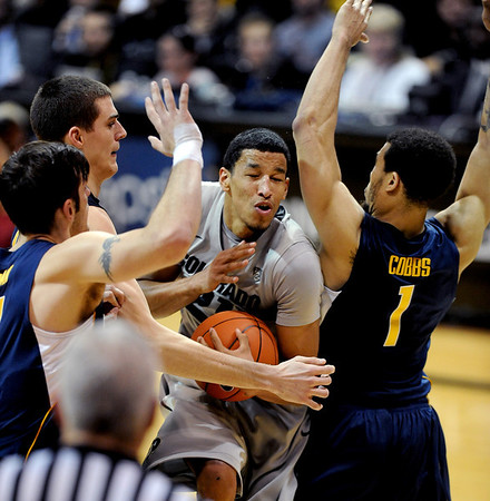 Andre Roberson goes strong to the basket past David Kravish, left and Justin Cobb both of Cal during the second  half of the January 27th, 2013 game in Boulder.<br /> Cliff Grassmick / January 27, 2013