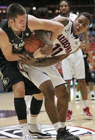 Arizona's Josiah Turner and Colorado's Austin Dufault fight for possession during the game. (AP Photo/John Miller)