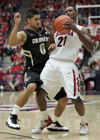 Arizona's Kyle Fogg struggles to hang on to the ball after being bumped by Askia Booker. (AP Photo/John Miller)