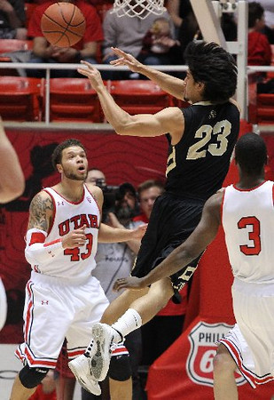 Colorado guard Sabatino Chen passes in front of Utah's Cedric Martin, left, during the first half. (AP)
